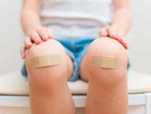 Kind mit Pflaster auf den Knien